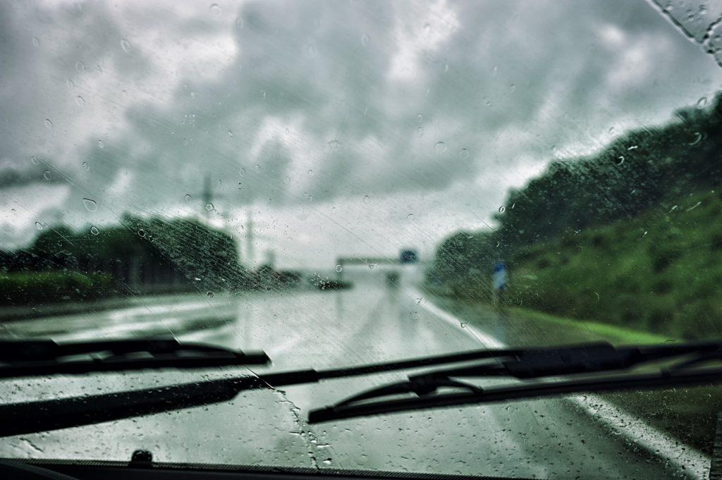 Autorijden in de herfst met regen en de regenwissers aan