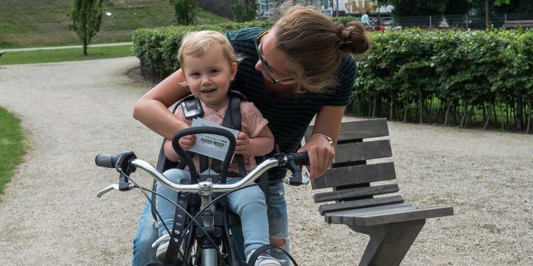 Fietsen met kinderen - moeder met lachend kind op fiets