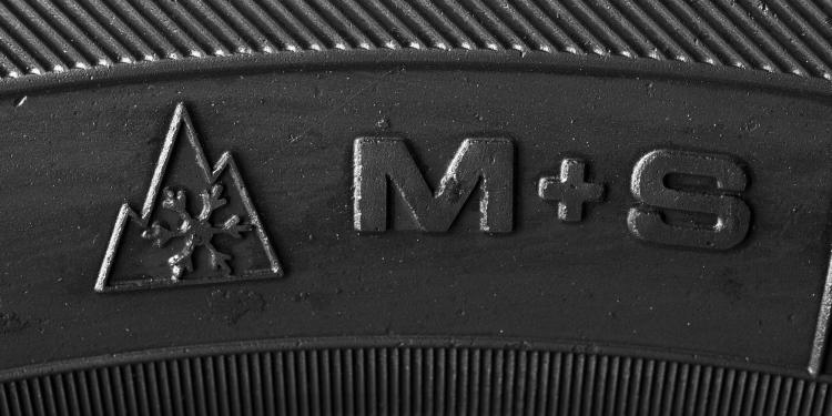 Zijkant autoband met symbolen M+S.