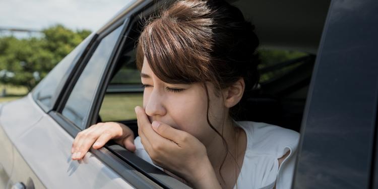 Wagenziekte: jonge vrouw wordt ziek tijdens rijden
